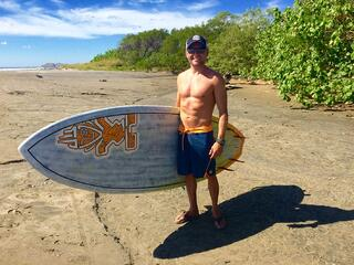 John smiling on the beach with his surfboard.